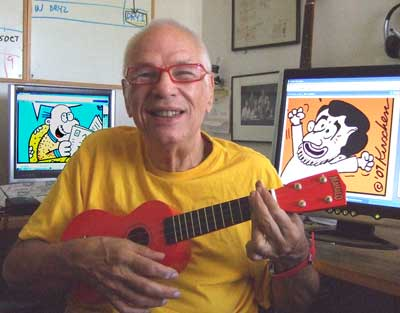 Dry Bones cartoonist strumming a Ukulele with Ahmadinejad and Mr.Shuldig cartoons on the computer screens behind him.